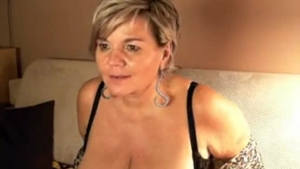 Mature German blonde is rubbing her partner's rock hard dick with her big tits, in her bedroom